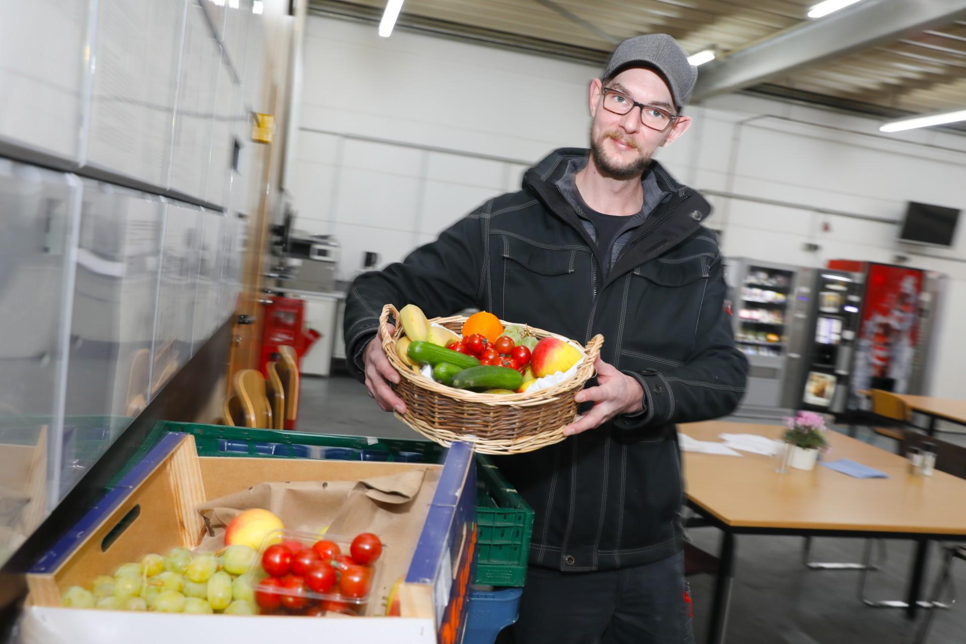 Unternehmen Familie Dücker Group - ein Mitarbeiter trägt einen gut gefüllten Obstkorb