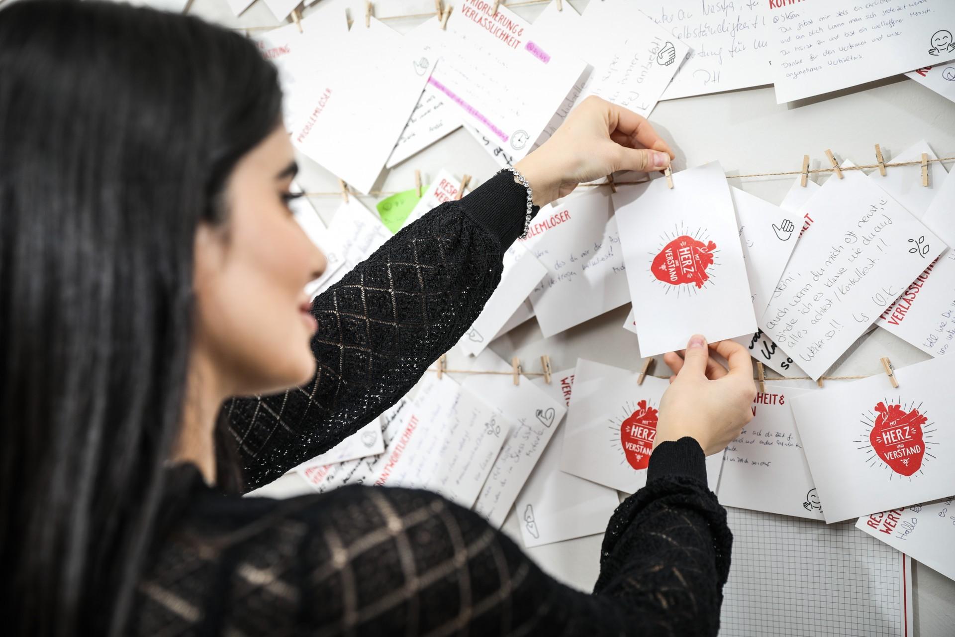 Tradtionsbetrieb mit Start-up-Mentalität, Mitarbeiterin hängt Zettel an die Lobleine